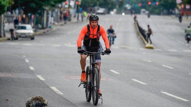 Un ciclista viaja por una carretera sin tráfico por la huelga en Caracas.