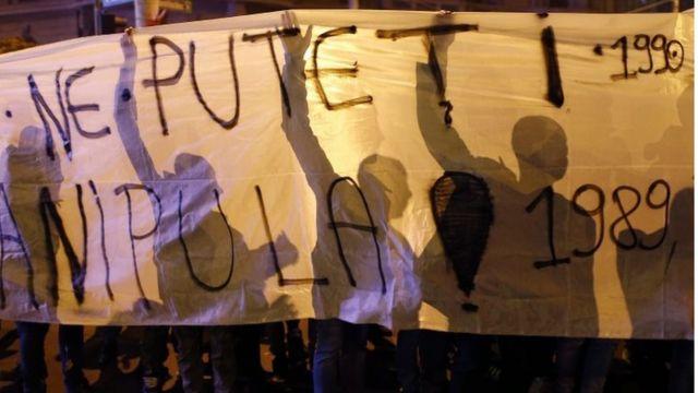 「我々を繰ることはさせない」「汚職は人を殺す」などと書かれた垂れ幕を掲げるデモ参加者(4日、ブカレスト市内)