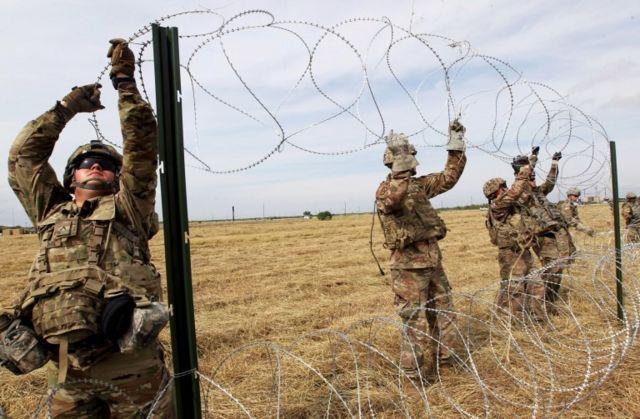 Soldados instalan alambre de púas en la frontera