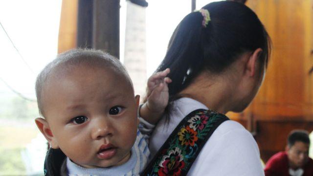 Bebê chinês nas costas de sua mãe