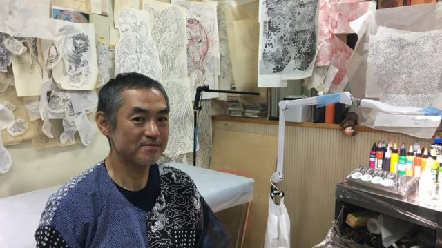 Tattoo artist Horimitsu sitting in his studio in Tokyo, where the walls are lined with tattoo sketches