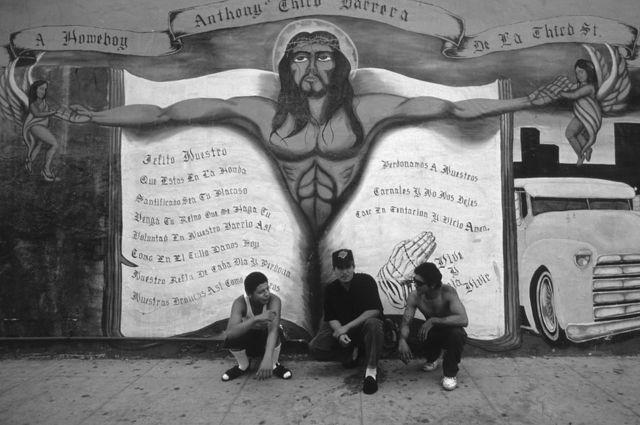 ثلاثة رجال يجلسون أمام رسم جداري يجسد المسيح في لوس أنجليس.