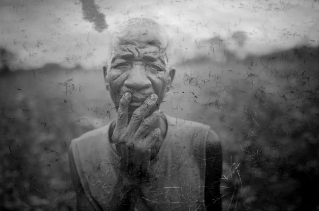 An elderly farmer stands in his field, overlaid onto an image of a puddle of murky water