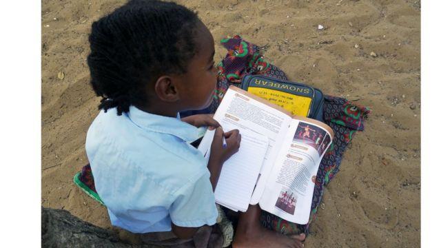 Jessica, de 8 anos, aluna da 3ª série, faz a lição de português sentada no chão