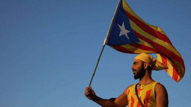 Un manifestantes hace ondear la bandera independentista de Cataluña.