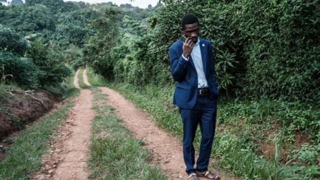 Presidential candidate Robert Kyagulanyi, also known as Bobi Wine, talks on the phone after talking to members of the media at one of his the gates of his home in Magere, Uganda, on January 15, 2021.