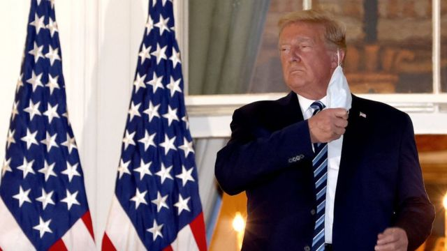 U.S. President Donald Trump removes his mask upon return to the White House from Walter Reed National Military Medical Center on October 05, 2020 in Washington, DC