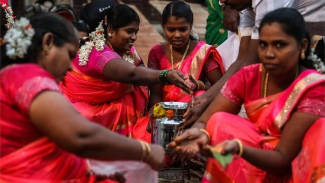 Tamilian women cook pongal, a traditional rice dish, during the Thai Pongal festival celebration in Mumbai, India, 15 January 2020