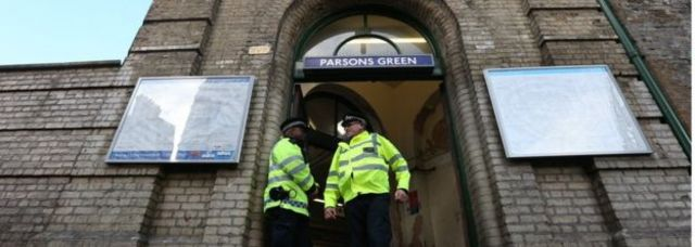 Dois policiais em frente à porta da estação de metrô Parsons Green