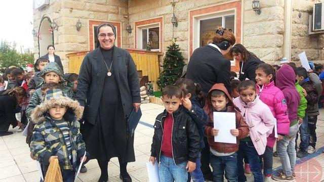 Irmã Sanaa Hana é a superiora das Irmãs do Sagrado Coração. Seu convento em Mossul foi destruído pelo grupo Estado Islâmico. A foto mostra a irmã Sanaa em Erbil com crianças em frente a uma casa da congregação onde ela encontrou refúgio.