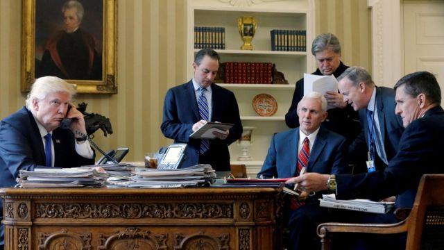 Trump hablando por teléfono rodeado por su equipo de gobierno al principio de su mandato.