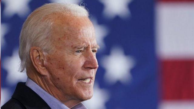 Joe Biden com bandeira americana ao fundo