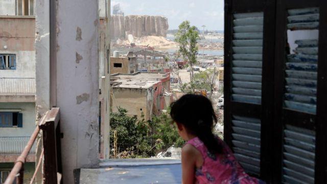 طفلة تنظر إلى الدمار