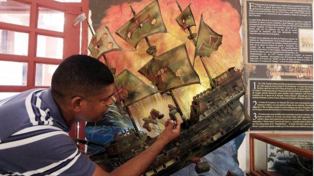 Un hombre observa una ilustración del galeón español San José, durante una rueda de prensa para anunciar el descubrimiento del naufragio, en Cartagena, Colombia, 5 de diciembre de 2015.