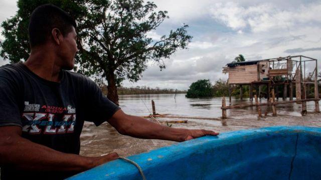 persona navega sobre una calle inundada