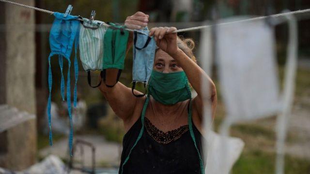 Una mujer colgando mascarillas recién lavadas en un cordel.