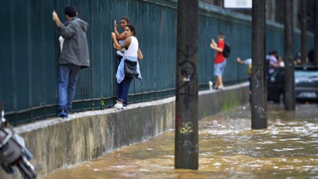 People climb along a fence to pass a flooded area