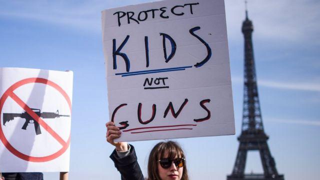 """Девојка носи паролу """"Заштите децу а не оружје"""" на протесту подршке за """"Марш за наше животе"""" у Паризу на коме су се окупили Французи и Американци који живе у Француској"""