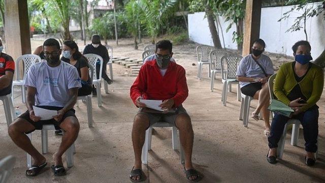Pessoas sentadas usando máscara