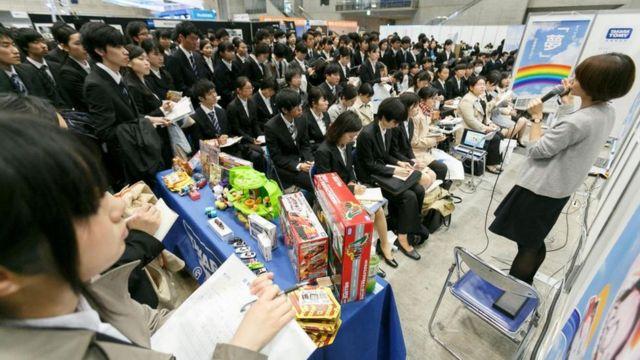 Theo truyền thống, sinh viên đại học Nhật Bản tham dự các buổi thuyết trình từ các nhà tuyển dụng của công ty trong mùa tìm việc làm 'shūshoku katsudō', hoặc shūkatsu