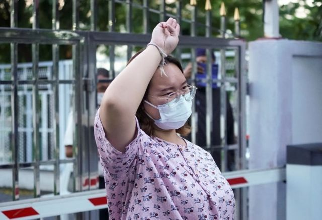 """Protest leader Panusaya """"Rung"""" Sithijirawattanakul, who has spent eight weeks in detention on charges of insulting the country""""s king, shows a three-finger salut as she leaves after she was granted bail at the Central Women""""s Correctional Institute in Bangkok, Thailand, May 6, 2021."""