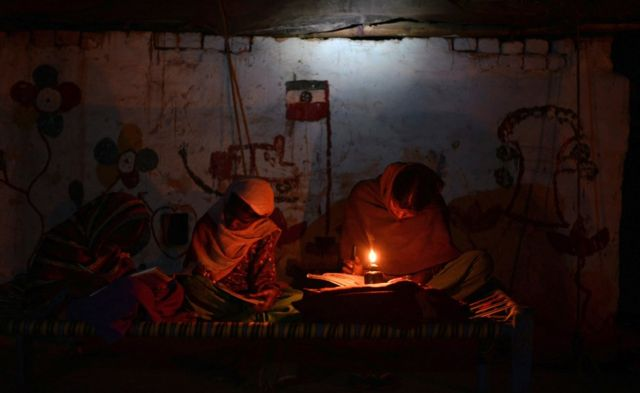 Indian girls study by candle light in a slum without electric power in the town of Jalandhar