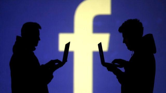 Sombra de duas pessoas mexendo em laptops à frente de grande logomarca do Facebook