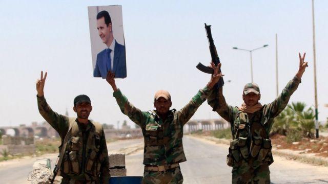 Militares con una foto de Bashar al Asad