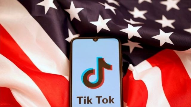 "TikTok""s logo is displayed on the smartphone while standing on the U.S. flag in this illustration picture taken, November 8, 2019."