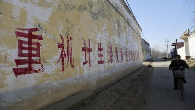 """A resident rides a bicycle past a slogan on the wall which partially read """"Pay attention to One-Child Policy and seek developments"""", at a village in Handan, Hebei province, China, December 2014."""