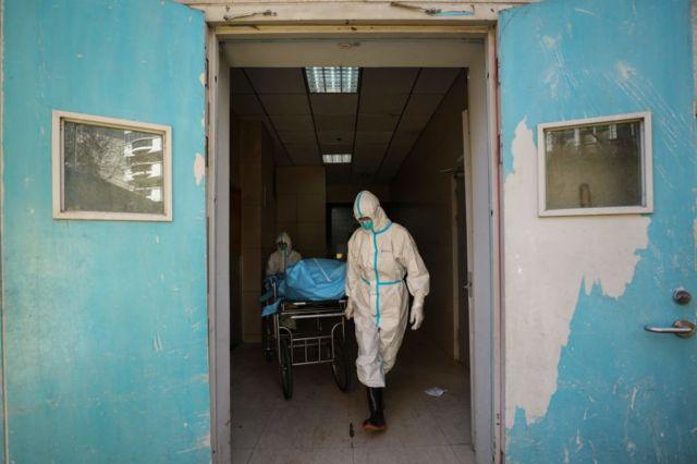 武漢兩名醫護人員正在搬運一名新冠肺炎患者的遺體。