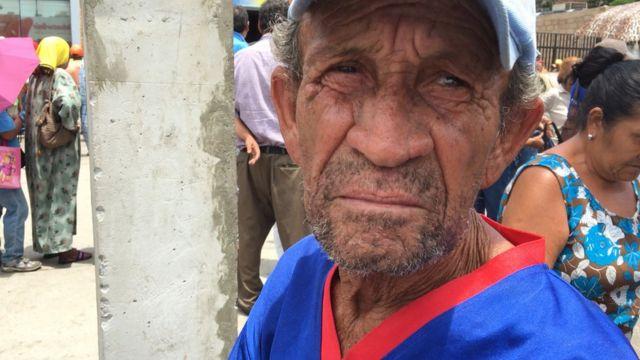 Aposentado e outras pessoas em fila para sacar dinheiro na Venezuela