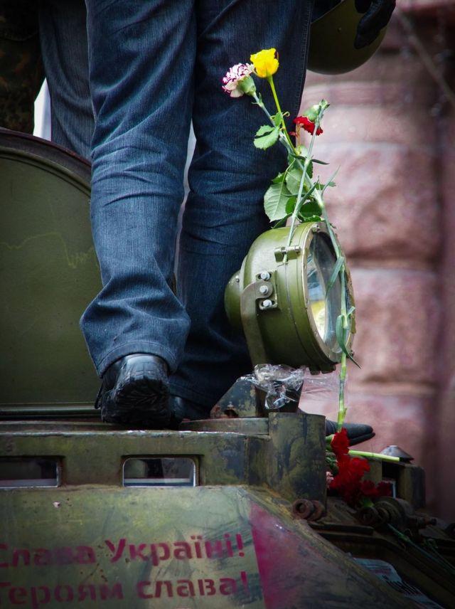 Людина з каскою біля квітів