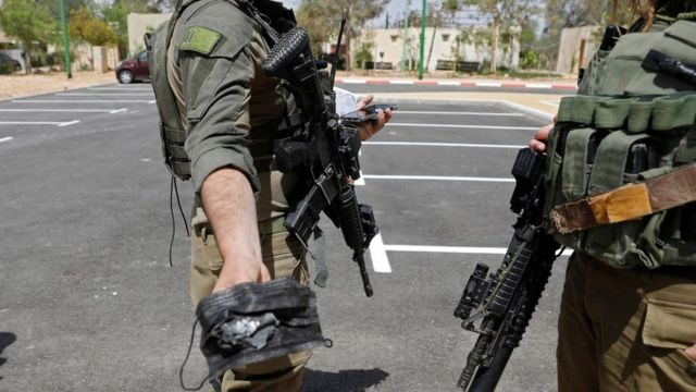 An Israeli soldier holds up an apparent missile fragment found in southern Israel (22 April 2021)