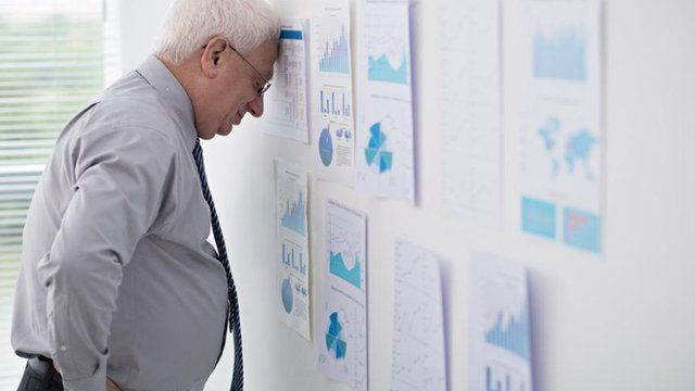Businessman overwhelmed by spreadsheets