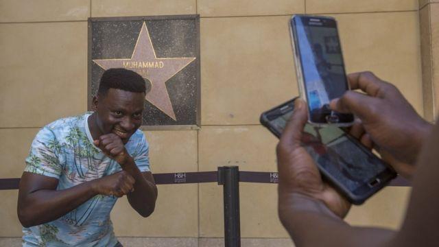Eric Obeng, umunya Ghana, yiga muri kaminuza muri Amerika, ariko yifotoza mu kwibuka igihangange mw'iteramakofe yitavye Imana, Muhammad Ali, kukimeneytso c' inyenyeri ciwe mu bitonze kw'ibarabara rya Hollywood Walk of Fame kuwa gatandatu 04/06/2016...
