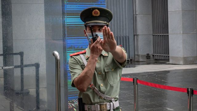 """A Chinese police officer gestures """"stop"""" outside the Australian embassy in Beijing in July 2020"""