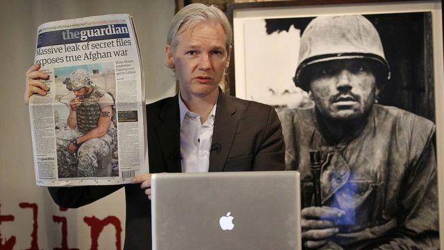 Julian Assange con un periódico