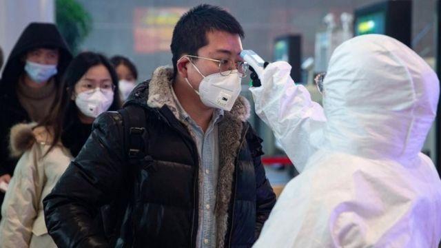 Profissional de saúde faz medição de temperatura em cidadão na China