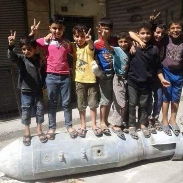 Abana bakinira hejuru y'igisasu mu gace ka al-Muyaser mu mujyi wa Aleppo.