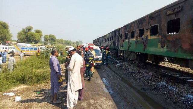 Authorities stand by the charred wreckage of the train in Pakistan