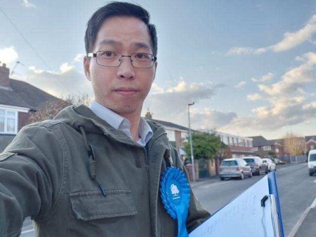 Timothy Cho berfoto dengan memakai roset Partai Konservatif