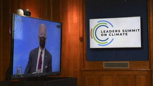 Biden aparece de máscara em tela de televisão, ao lado de painel com símbolo da cúpula do clima