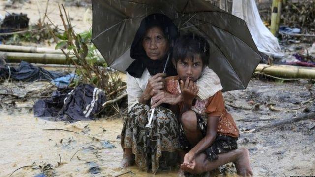 "Rohingya refugees shelter under an umbrella during rain in Bangladesh""s Balukhali refugee camp."