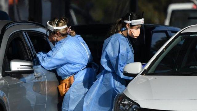 Hai nhân viên y tế kiểm tra những người trong ô tô