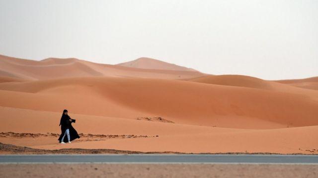A Saudi girl plays in the sand dunes near Buraydah, 400 kms northwest Riyadh on March 11, 2016