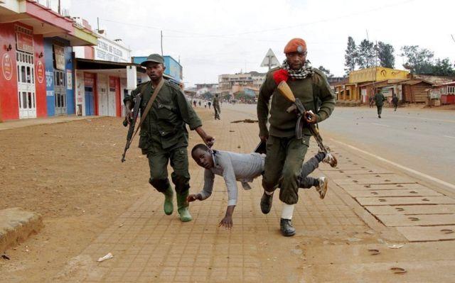 कांगो में नस्लीय हिंसा के एक संदिग्ध को पकड़ कर ले जाती हुई पुलिस