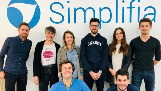 Funcionários posam para foto em frente a painel com nome Simplifia