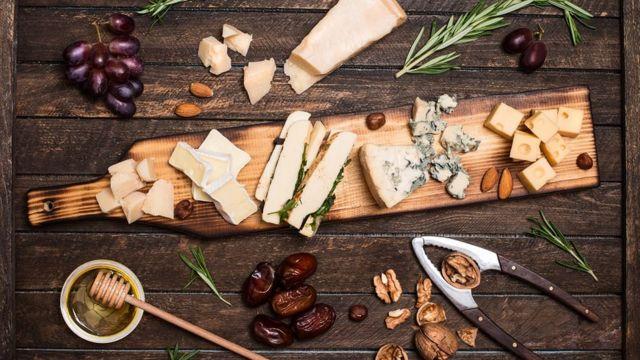 Un plateau de fromage bien chargé, entouré d'amandes, de raisins rouges, de dattes, de miel, de branches de romarin et de noix.