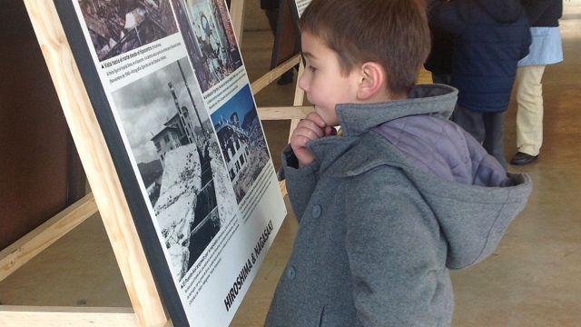Un niño mira ensimismado un cartel sobre la bomba de Hiroshima en una exposición en Valdivia, Chile
